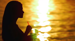Woman silhouette with cocktail, drink and dream on the beach Stock Footage