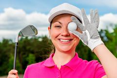 comic portrait of a beautiful girl with a ball and putter - stock photo