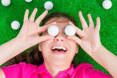 comical portrait of a girl with golf balls - stock photo