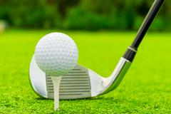 ball and putter close-up on green grass - stock photo