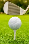 Vertical shot the putter and golf ball on a lawn - stock photo