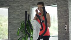 Young woman listening to music while exercising on elliptical machine at home Stock Footage