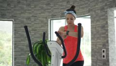 Young woman checking pulse on smartwatch on elliptical machine - stock footage