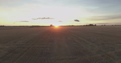 Flight over a field towards the sunset Stock Footage