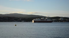 The ship hurtigruten leaving tromsoe city harbour in autumn sunshine zoom out Stock Footage