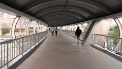 POV walk through modern skybridge, people passing covered open-air pedway Stock Footage