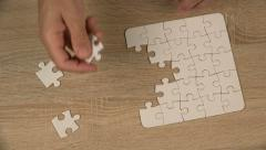 Man completing jigsaw puzzle Stock Footage