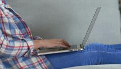Midsection of woman typing on laptop lying on sofa - stock footage