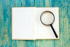 Stock Photo of Open book and magnifier