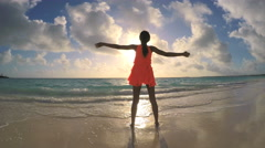 Young barefoot ethnic female in red dress dancing on sunset beach - stock footage