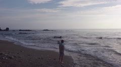 the view from air the boy fishes on an ocean coast - stock footage