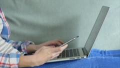 Female typing on laptop keyboard and checking smart phone Stock Footage