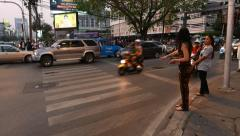 Young thai woman flag and grab motorcycle taxi on lively junction, dusk time Stock Footage