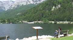 4k Woman sitting viewpoint alps lake landscape Austria Stock Footage