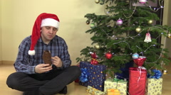 Man eat delicious Santa form chocolate near Christmas fir tree Stock Footage