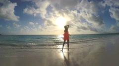 African American girl in red dress enjoying beach sunrise - stock footage