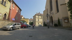 Cars parked in front of the Monastery Church in Sighisoara Stock Footage