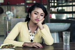 Sad, unhappy woman sitting by table at kitchen at home NTSC - stock footage