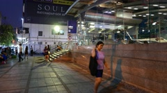 Commuters walk outside metro station, glass walled pavilion, late evening Stock Footage