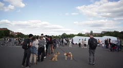People wait in line for art refugee installation boat raft in Berlin Tempelhof Stock Footage