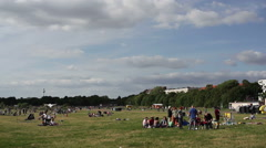 People have picnic in Berlin Tempelhof Airport park, tv tower behind Stock Footage