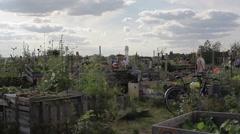 People walk around community garden on sunny day, pan right - stock footage