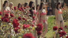 Models in bikinis going through the green park - stock footage