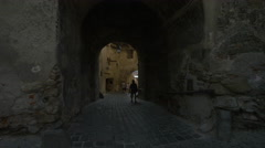 Walking under the arches from Turnului Street in Sighisoara Stock Footage