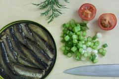 Sprats, onion and tomatoes on a cutting board Stock Photos