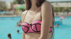 Slender girl with long straight hair wearing a pink swimsuit posing near the Stock Footage