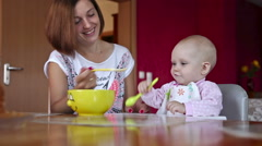 Beatiful girl feeds her baby Stock Footage