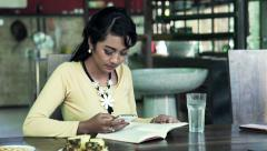 Young asian woman reading book and using smartphone sitting by table at home Stock Footage