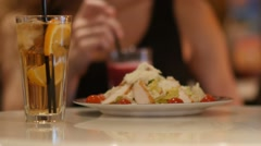Girl in cafe, sipping cocktail, salad on foreground, selective focus. Stock Footage