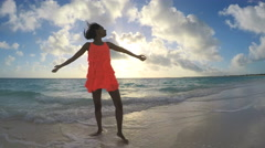 African American girl in red dress barefoot on sunset beach Stock Footage