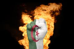 fire fist with the national flag of algeria - stock photo