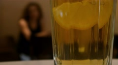 Girl in cafe, talking by phone, glass of cocktail on foreground, selective focus - stock footage