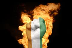 Fire fist with the national flag of cote divoire Stock Photos