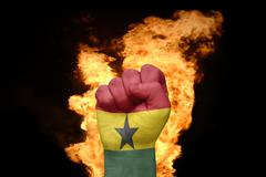 fire fist with the national flag of ghana - stock photo