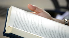 Woman reading book in a park Stock Footage