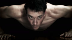 Man doing Push-ups isolated on a black Background Stock Footage