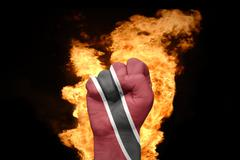 fire fist with the national flag of trinidad and tobago - stock photo