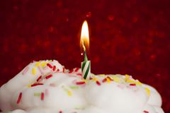 Cupcake with a lit candle over bright red background Stock Photos
