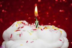 Stock Photo of Cupcake with a lit candle over bright red background