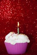 Cupcake with a lit candle over bright red background - stock photo