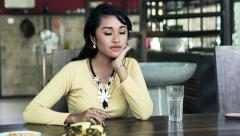Impatient, sad asian woman waiting for someone while sitting by table at home - stock footage