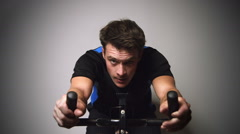 Motivated Young Man Sprinting and Sweating on a Stationary Bike Stock Footage