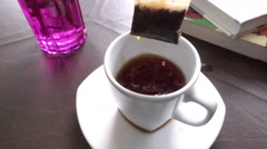 Close up of man pulling a tea bag from hot water in a white cup, slow motion Stock Footage