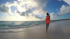 African American girl in red dress barefoot on sunset beach - stock footage