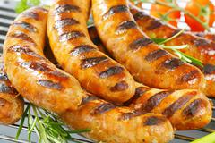Grilled bratwursts on barbecue grid - stock photo