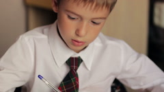 Boy student closeup in a white shirt and tie doing homework sitting at a table Stock Footage